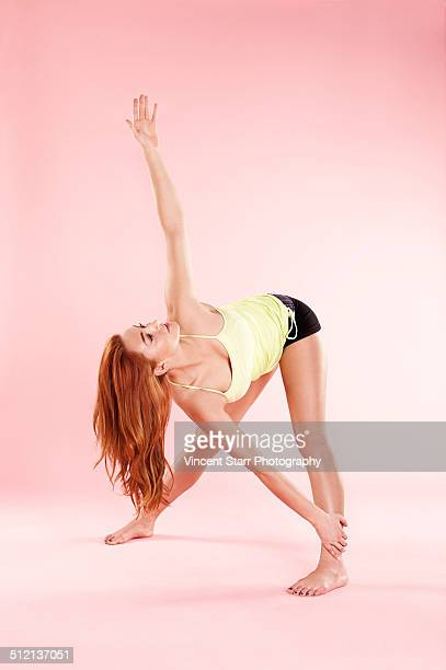 Studio shot of young woman in yoga position twisting with arm raised