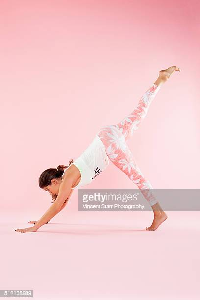 Studio shot of young woman in yoga position with hands on floor and leg raised