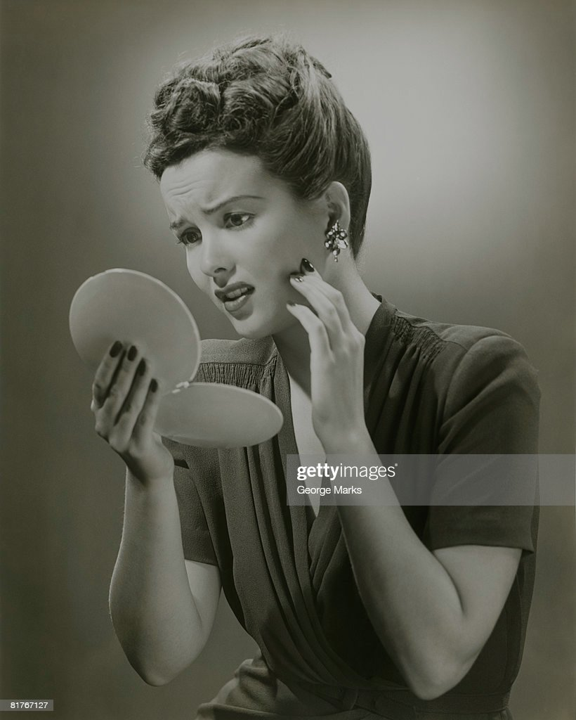 Studio shot of young woman looking in hand mirror : Stock Photo