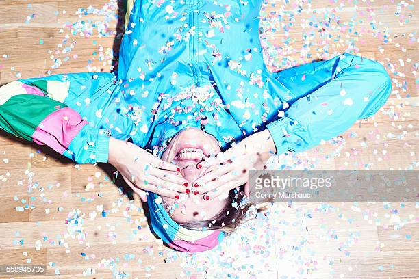 Studio shot of young woman lying on floor covered in confetti