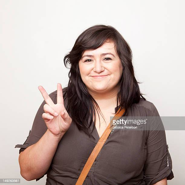 studio shot of young woman making peace sign - chubby photos et images de collection