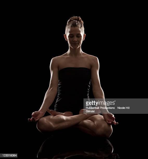 Prise de vue en Studio de jeune femme méditer en position du lotus, padmasa