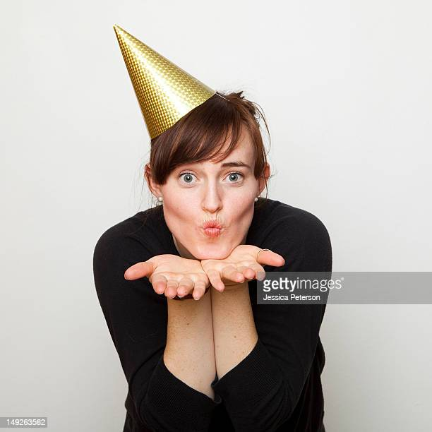Studio Shot of young woman party hat blowing kiss
