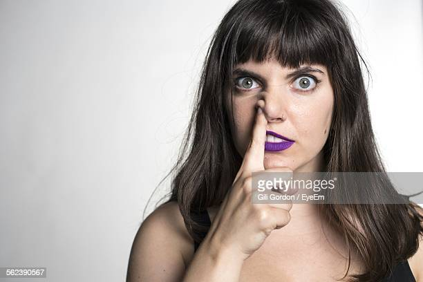 Studio Shot Of Young Woman Picking Nose