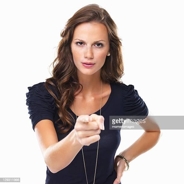 Studio shot of young woman pointing at camera