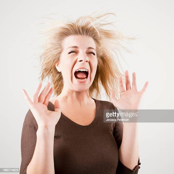 Studio shot of young woman screaming