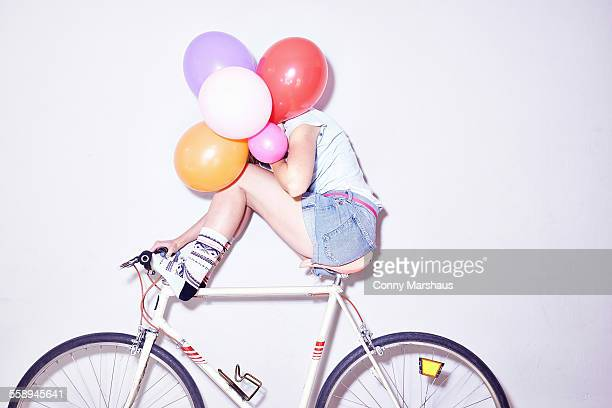 studio shot of young woman sitting on bicycle hiding behind bunch of balloons - verlegen stockfoto's en -beelden