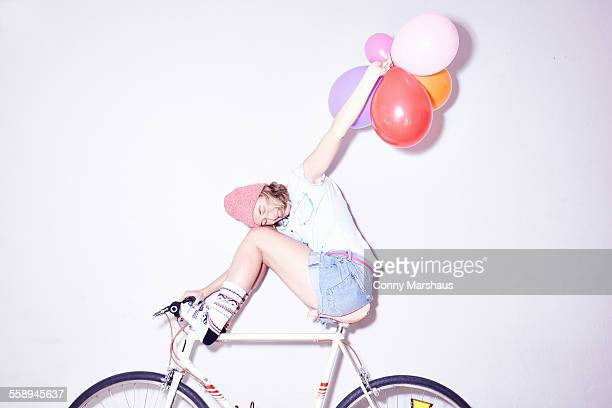 Studio shot of young woman sitting on bicycle holding up bunch of balloons