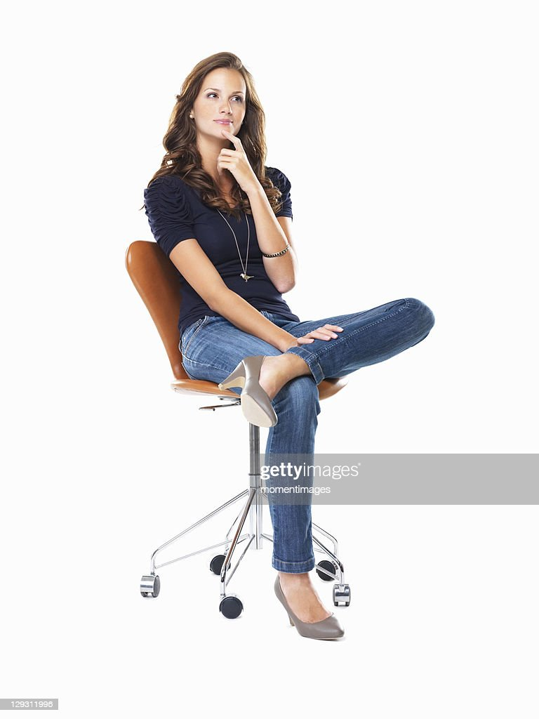 Studio Shot Of Young Woman Sitting On Chair And Thinking