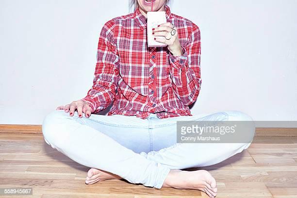 Studio shot of young woman sitting on floor drinking juice