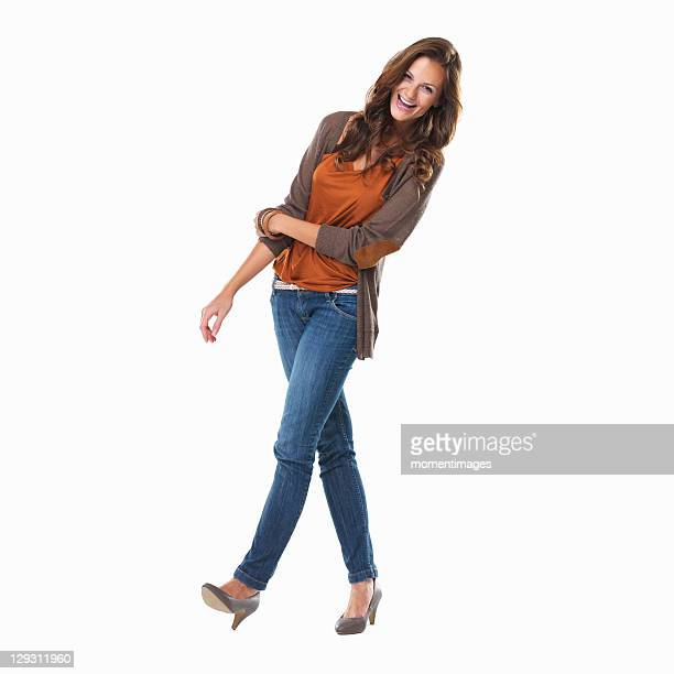 Studio shot of young woman smiling and walking