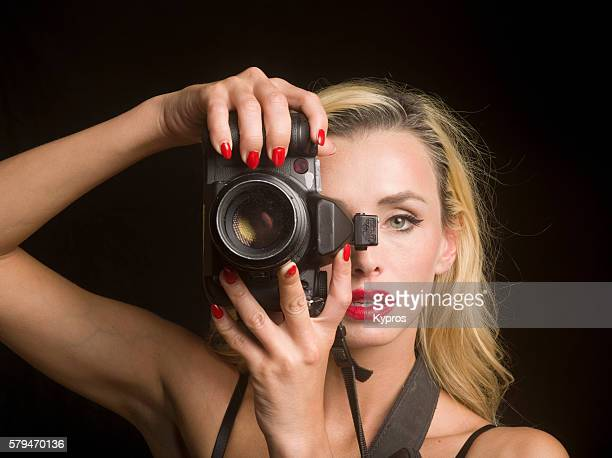 Studio Shot Of Young Woman Taking Pictures With A D-SLR Digital Camera