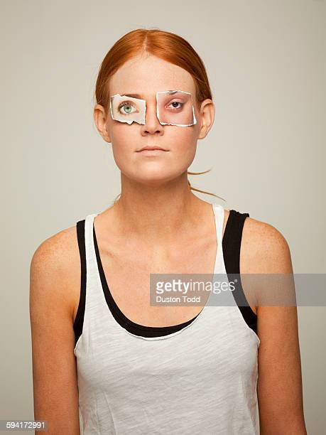 Studio shot of young woman top artificial paper eyes