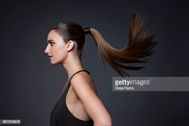 studio shot of young woman tossing hair - ponytail stock pictures, royalty-free photos & images