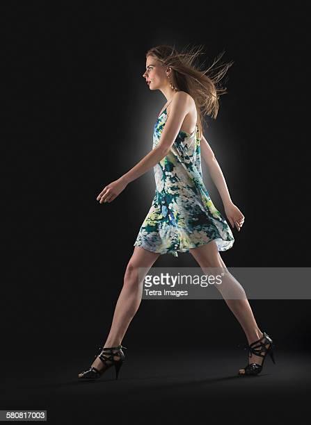 Studio shot of young woman walking