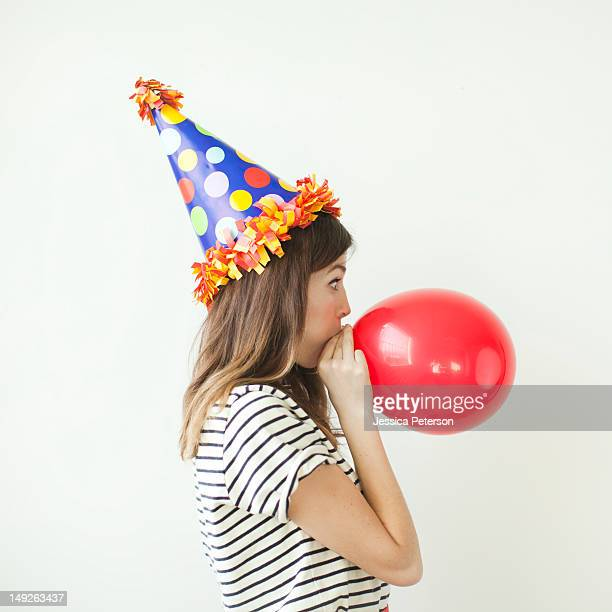 Studio shot of young woman wearing party hat and blowing balloon