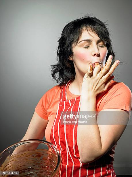 Studio shot of young woman with eyes closed licking chocolate from fingers