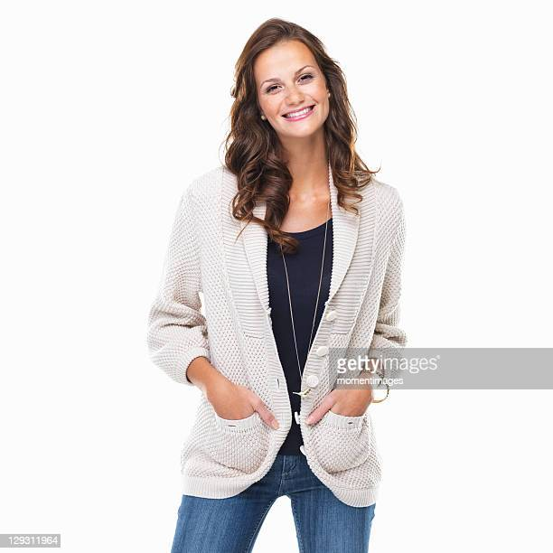 studio shot of young woman with hands in pockets and smiling - mains dans les poches photos et images de collection