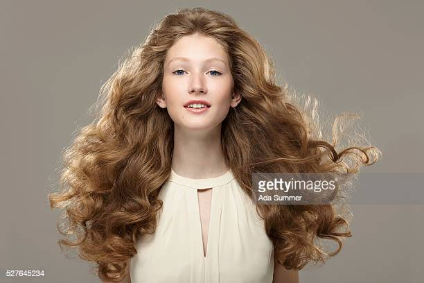 studio shot of young woman with long curly hair - wavy hair stock pictures, royalty-free photos & images