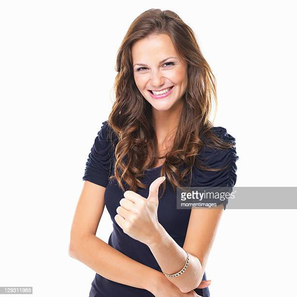 Studio shot of young woman with thumbs up