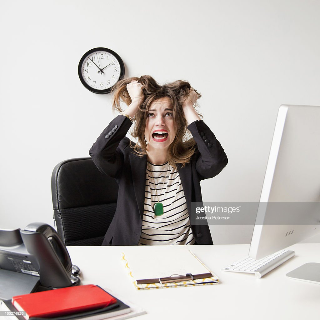 Studio shot of young woman working in office and tearing her hair out : Stock Photo