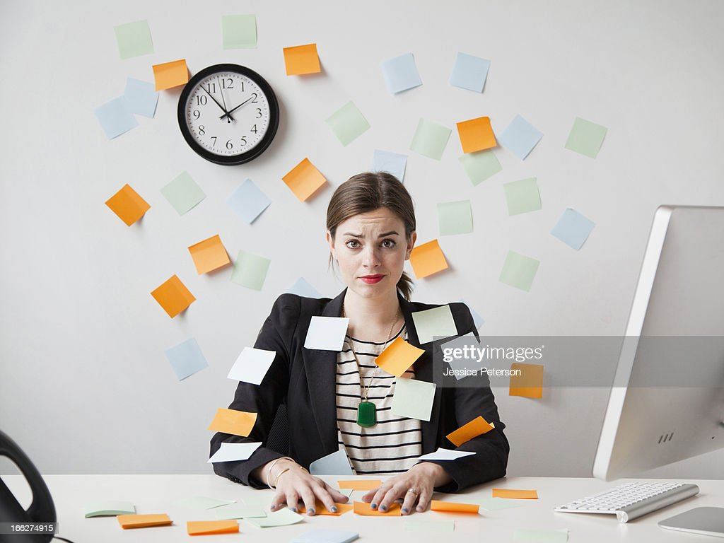 Studio shot of young woman working in office covered with adhesive notes : 圖庫照片
