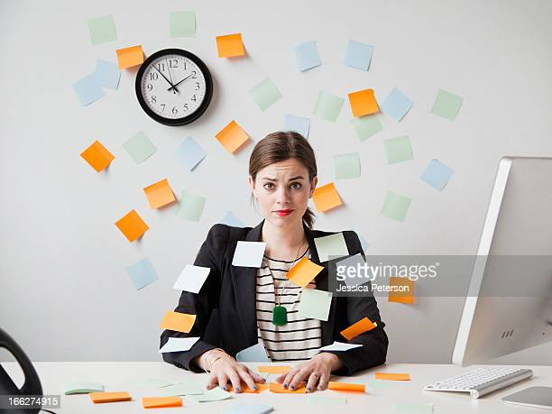 studio shot of young woman working in office covered with adhesive notes - stress stock-fotos und bilder