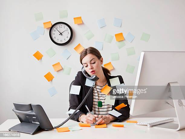 studio shot of young woman working in office covered with adhesive notes - multi tasking stock pictures, royalty-free photos & images