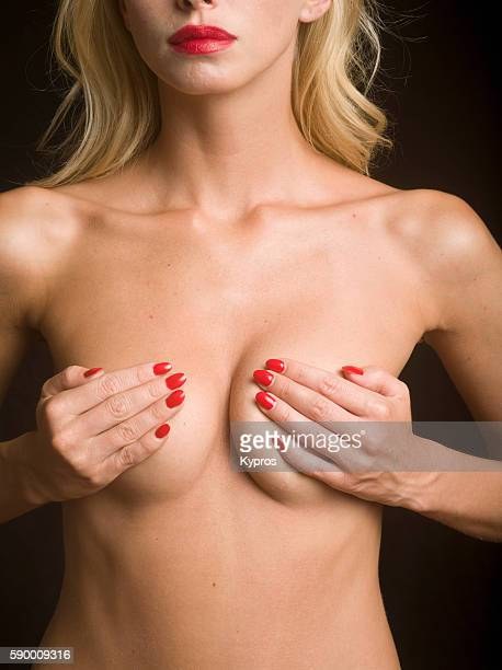Studio Shot Of Young Woman's Hand Touching Her Breast During Self-Examination
