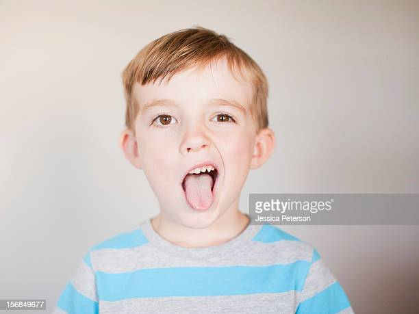 studio shot, portrait of boy sticking out his tounge. - grimacing stock pictures, royalty-free photos & images