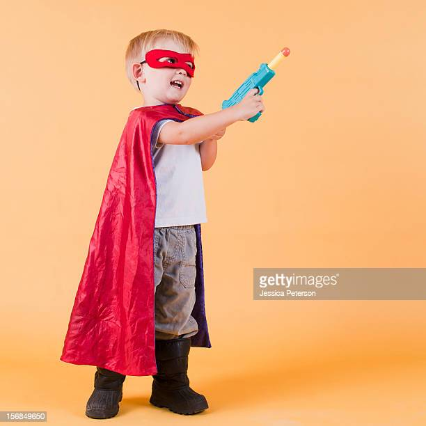 Studio shot, Portrait of boy (2-3) wearing cape and holding toy gun.