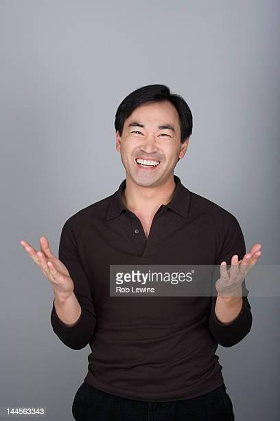 Studio shot portrait of mature man with hands raised, waist up