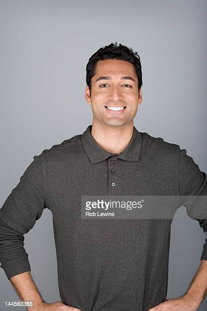 studio shot portrait of mid adult man with hands on hip, waist up - polo shirt stock pictures, royalty-free photos & images
