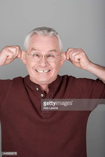 Studio shot portrait of senior man pulling his ears, head and shoulders
