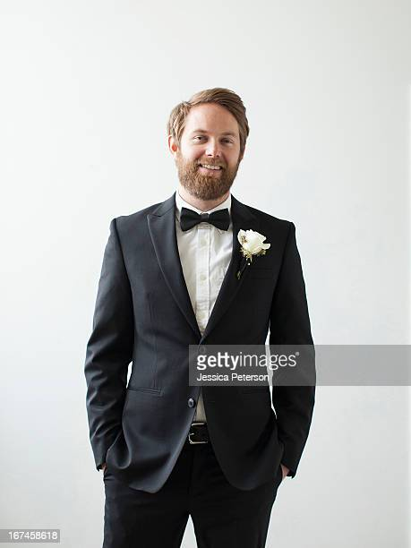 Studio Shot portrait of smiling groom with hands in pockets