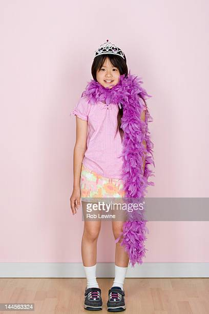 Studio shot portrait of teenage girl in diadem and feather boa shawl, full length