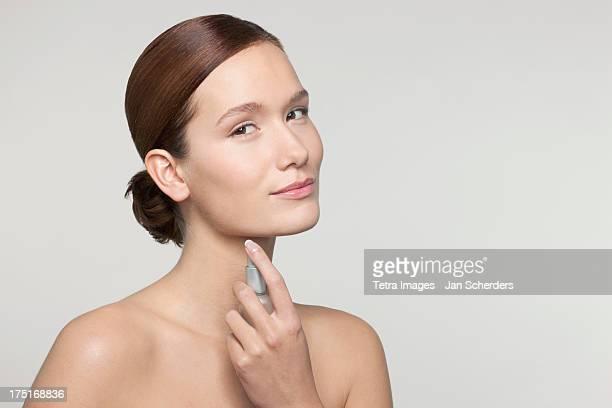 Studio shot portrait of young woman holding perfume