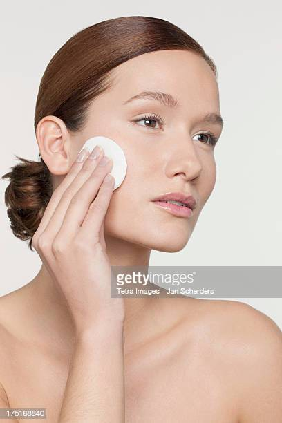 Studio shot portrait of young woman purifying her face with cotton pad