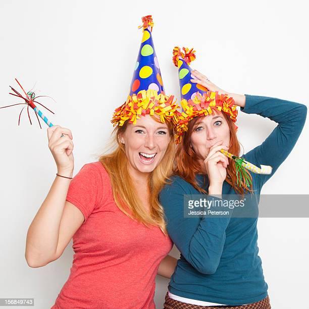 Studio Shot, Two young women wearing party hats.