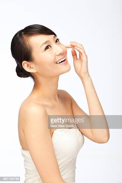 studio shot young woman doing facial - 頬 ストックフォトと画像