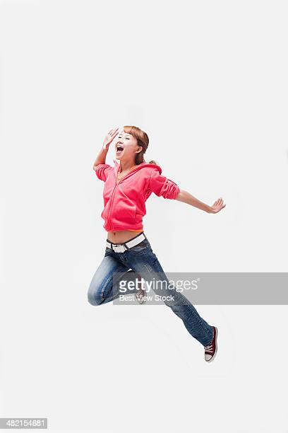 studio shot young woman jumping