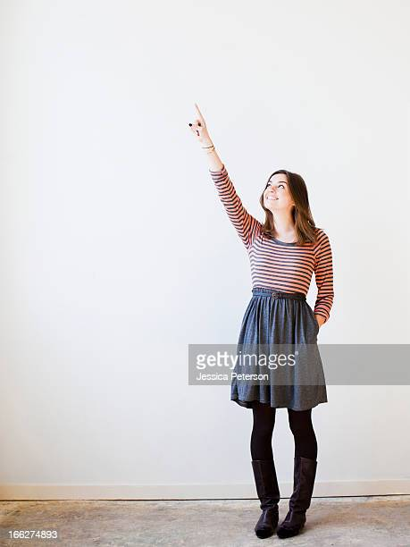 studio shot young woman looking up and pointing - skirt stock pictures, royalty-free photos & images