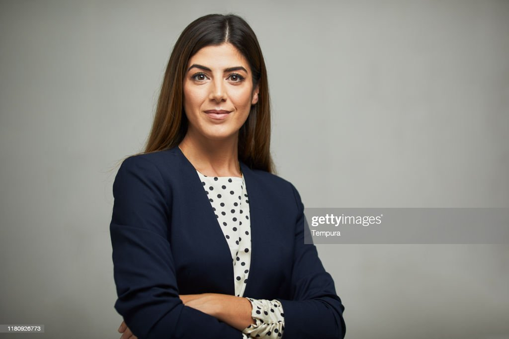Studio waist up portrait of a beautiful businesswoman with crossed arms. : Stock Photo