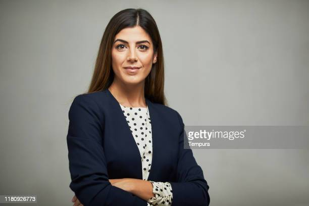studio waist up portrait of a beautiful businesswoman with crossed arms. - double breasted stock pictures, royalty-free photos & images