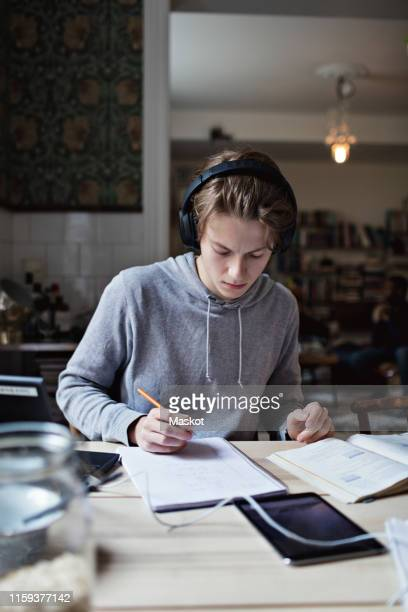 studious teenage boy listening music while studying on table at home - one teenage boy only stock pictures, royalty-free photos & images