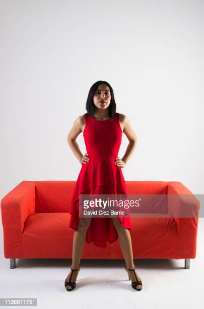 study session of young paraguayan woman with red dress and sofa - arms akimbo stock pictures, royalty-free photos & images