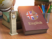 Studying and learn English concept. Book with flag of Great Britain and Big Ben tower on the table.