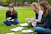 three friends study with flashcards outside