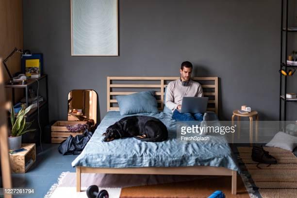 étudier/ travailler à la maison: un jeune homme utilisant son ordinateur portable dans le confort de sa chambre - grand angle photos et images de collection