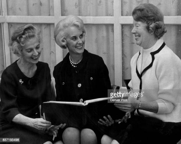 Studyingsealing arrangements for April 20 fashion show luncheon benefiting St Luke's Hospital Auxiliary are from left Mrs Lee Ashley Mrs Joseph Coors...